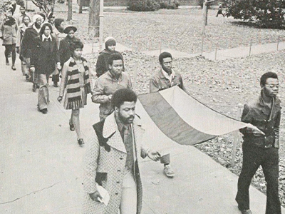 Students marching with a flag